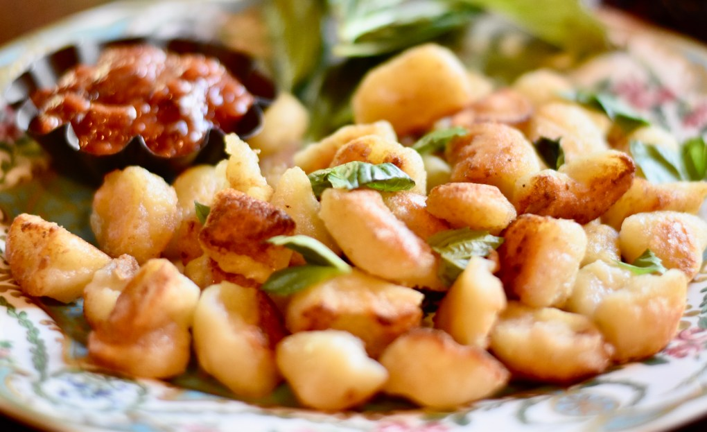A close up of the cauliflower gnocchi, a basil garnish, a dish of marinara on the side