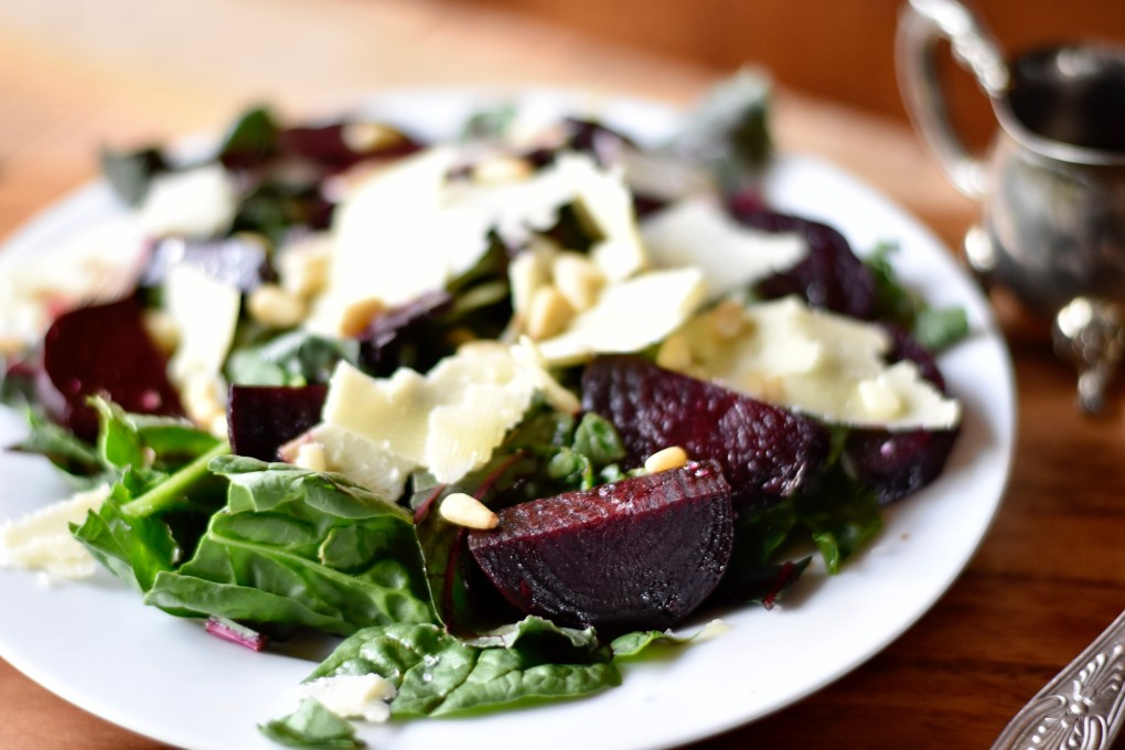 A close up of a beet salad, with lots of red beets and leaves.
