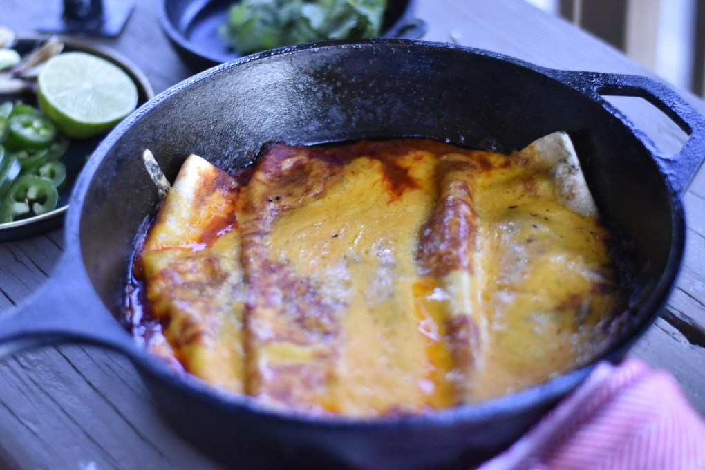 A close-up shot of a camping meal, including two cast iron pans, one with cilantro garnish, one with a very cheesy enchilada plate hot off the grill.