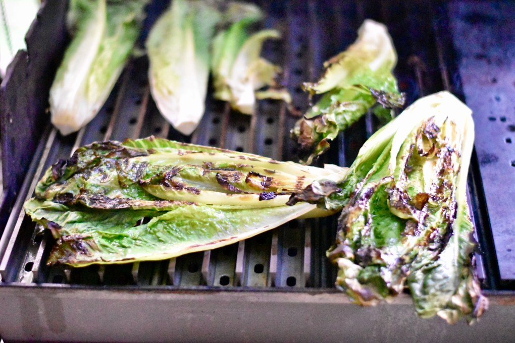 Grilled lettuce, on the grill, with Grill Grates visible underneath.