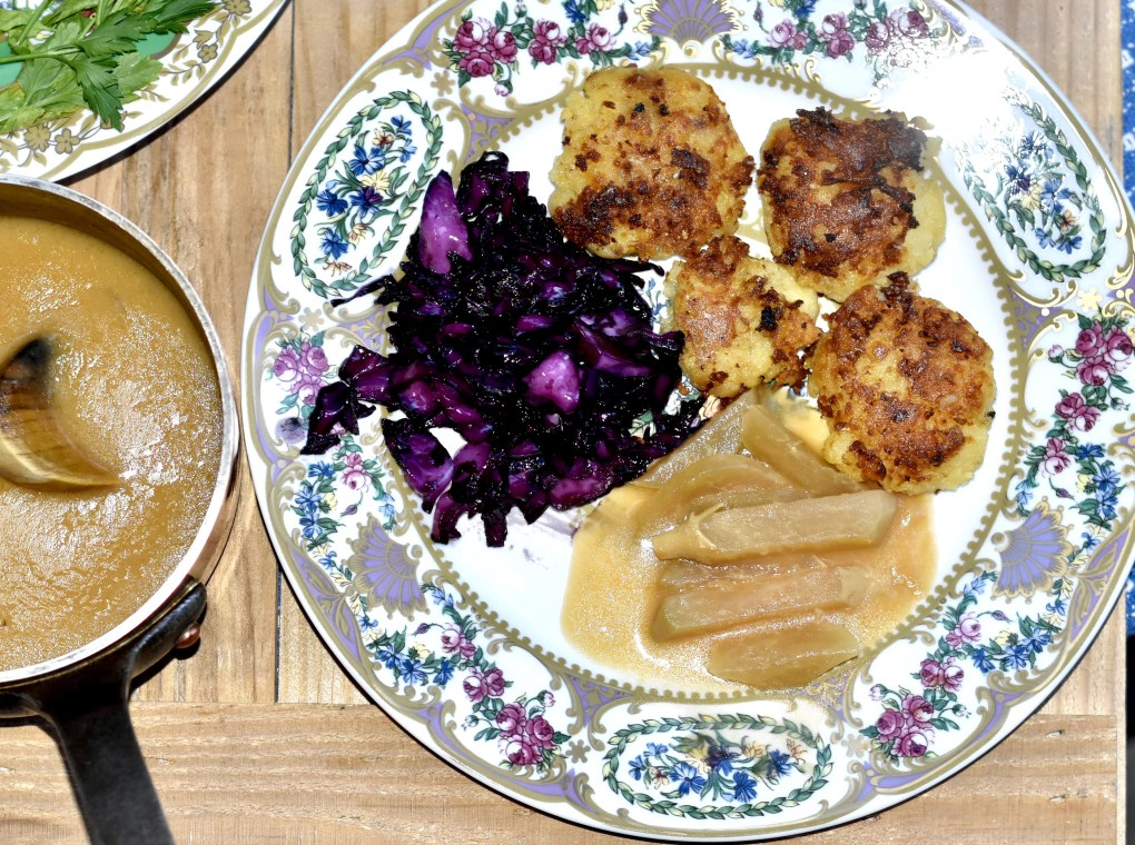 An overhead view of an ornate plate with a german meal, purple red cabbage on the left, kohlrabi in white sauce in the center, and potato frikadellen on the right. On the left is a sauce pan of  a thick brown sauce.