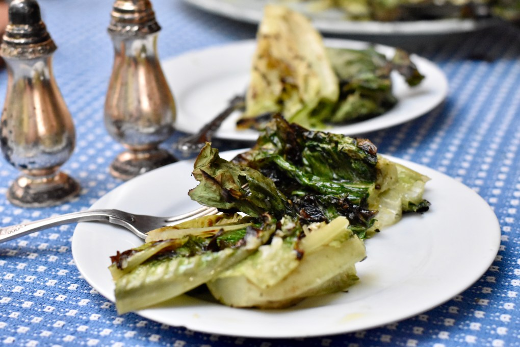 Close-up of the grilled lettuce with parmesan on a blue tablecloth with fancy salt and pepper shakers.