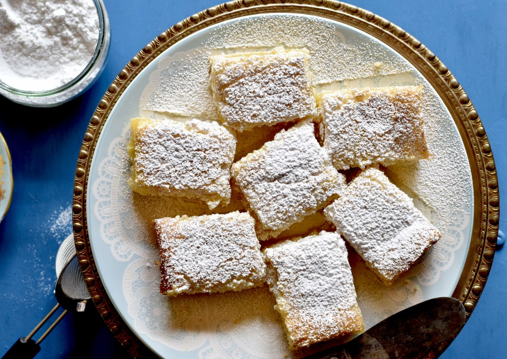 A tray of lemon bars, coated in powdered sugar.