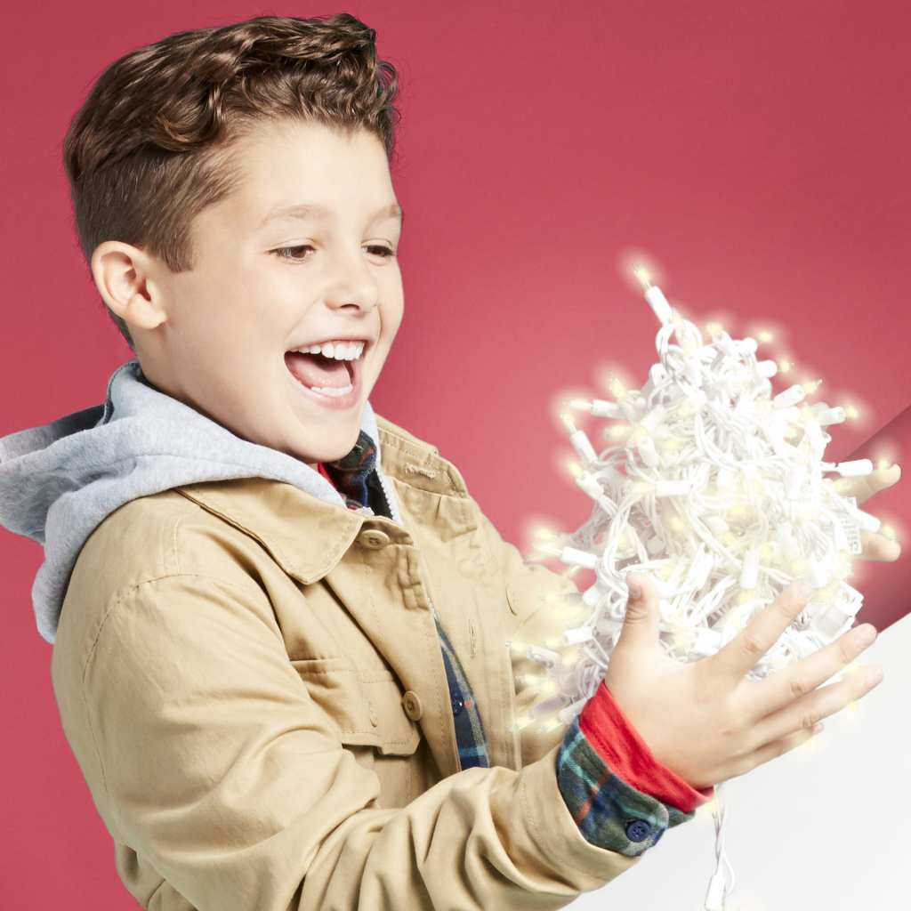 Boy looking at lit Christmas lights