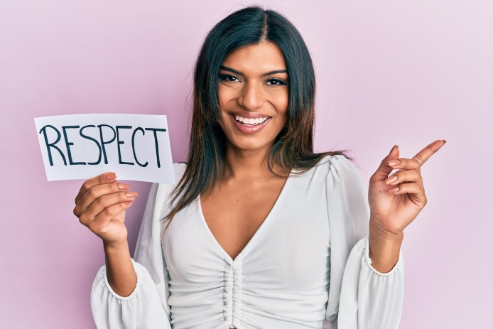 A young trans Latina in a white shirt smiles and holds a sign that says Respect