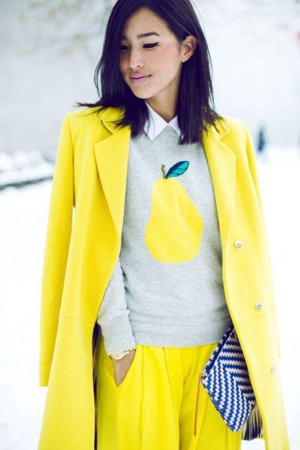 Modelo veste blazer, calça amarelo neon e blusa com detalhe do mesmo tom.