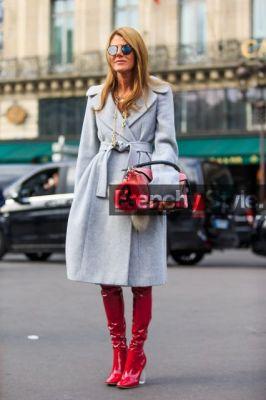modelo usa sobre tudo cinza fechado com bota vermelha cano longo em couro