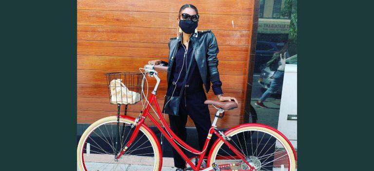 Jamiyla standing, masked, with a cruiser style bike