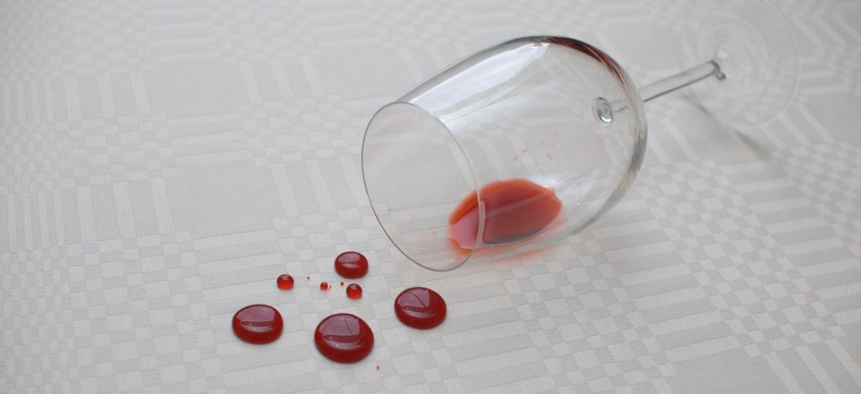 A wine glass on its side, with drops of spilled red wine on a white tablecloth