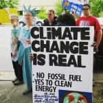 Lady Liberty and other protesters with sign that says Climate Change is Real -No fossil Fuel -Yes to Clean Energy