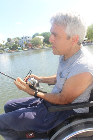 Mark Riffle using an attachment on his left arm to hold the fishing rod while he reels in with his right hand.