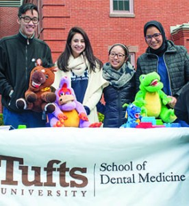 "10/04/2015 - Medford/Somerville, Mass. - Members of the Tufts School of Dental Medicine's ""Smile Squad"" pose at their table at Community Day on Oct. 4, 2015. (Evan Sayles for Tufts University)"