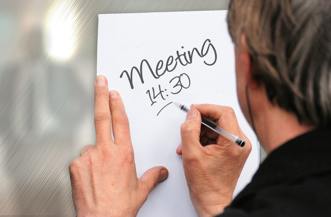 man writing a memo for a meeting