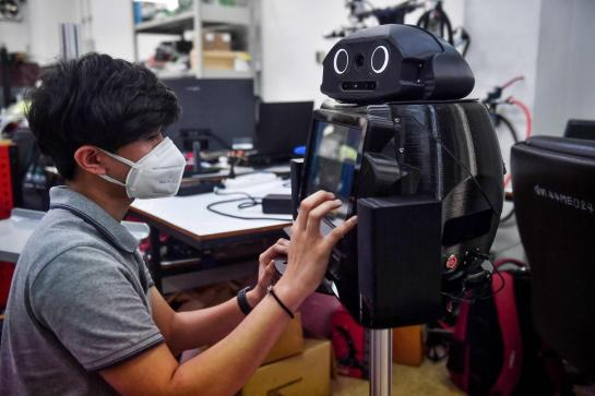 Tecnico programando el robot tailandes para combatir el coronavirus.