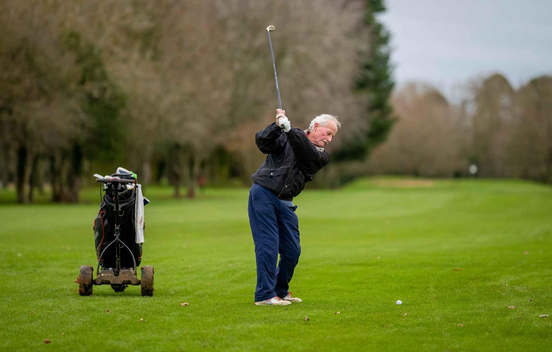 an elderly man playing golf