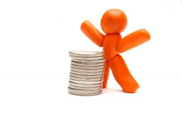 Plasticine figure staying in front of coins pile. Winner in business
