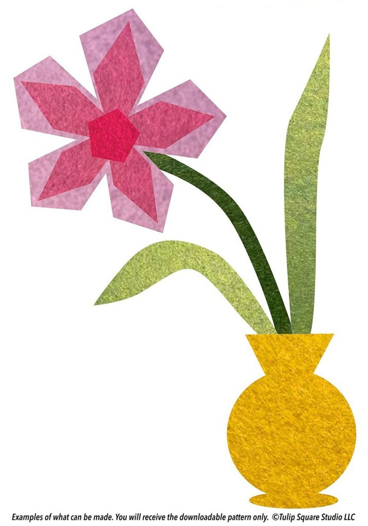 Stylized flower in shades of pink, in a yellow vase. All created with layers of felt appliqué.