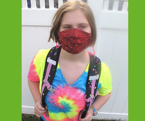 picture of a girl with a backpack wearing a mask and mask lanyard