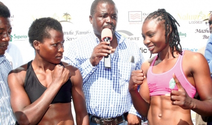 WORLD Boxing Council silver bantamweight champion Catherine Phiri (right) and Joyce Chileshe of Musenge Boxing Stables during weigh in at Nalumba 1 Lodge in Mongu yesterday. Looking on is Oriental Quarries Boxing Promotion director of operations Christopher Malunga.