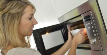 young woman cleaning microwave