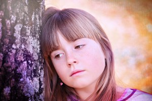 Tuned In Parents - sad tween girl leaning against tree