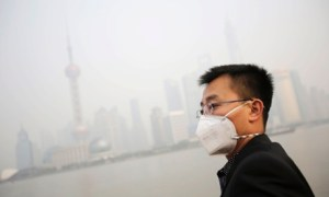 """A tourist with a protective mask watches the buildings at the Bund under heavy haze in Shanghai, China, Friday, Dec. 20, 2013. Shanghai's environmental protection bureau issued a """"yellow"""" pollution warning this afternoon and said it was taking """"emergency emission reduction"""" measures and recommends that children, the elderly and people suffering from heart disease or lung disease should stay indoors and cease outdoor exercises. (AP Photo/Eugene Hoshiko)"""