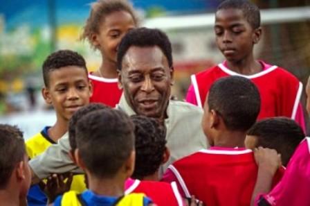 Pelé rodeado de niños en la inauguración de la cancha ecológica. Foto AFP