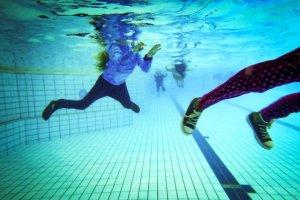 Para obtener el certificado de natación, los niños practican vestidos en las piscinas