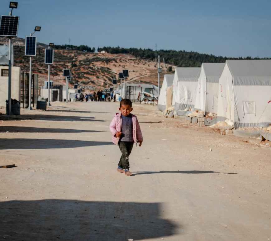 ethnic boy walking in refugee camp