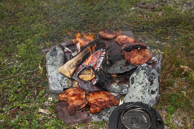 ..og lar de ligge til varming på steinene rundt bålet