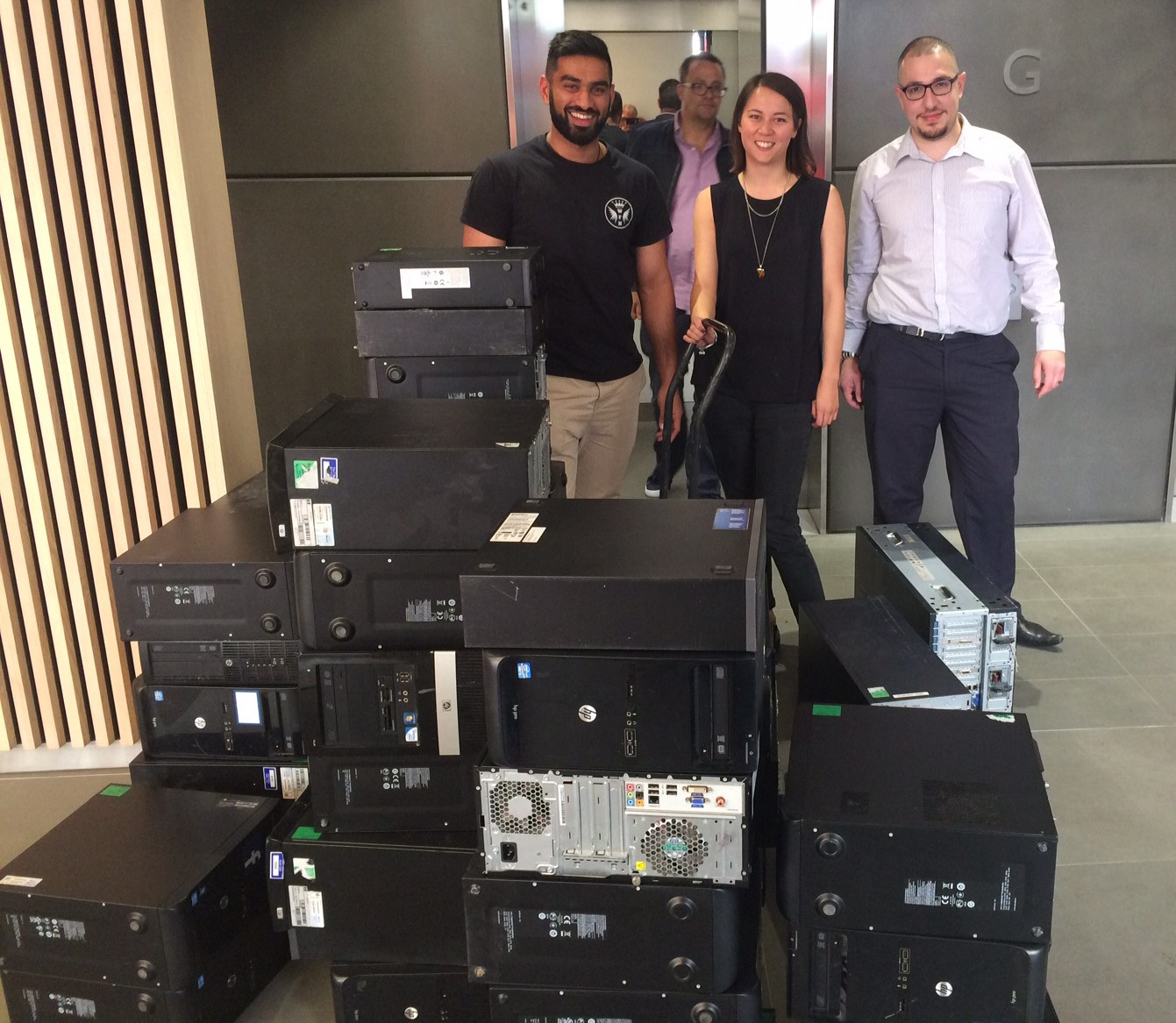A group of supporters of The Turing Trust with donated IT equipment.