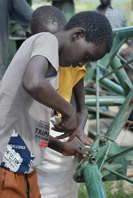 Young boys eager to help tighten bolts of the wind pump
