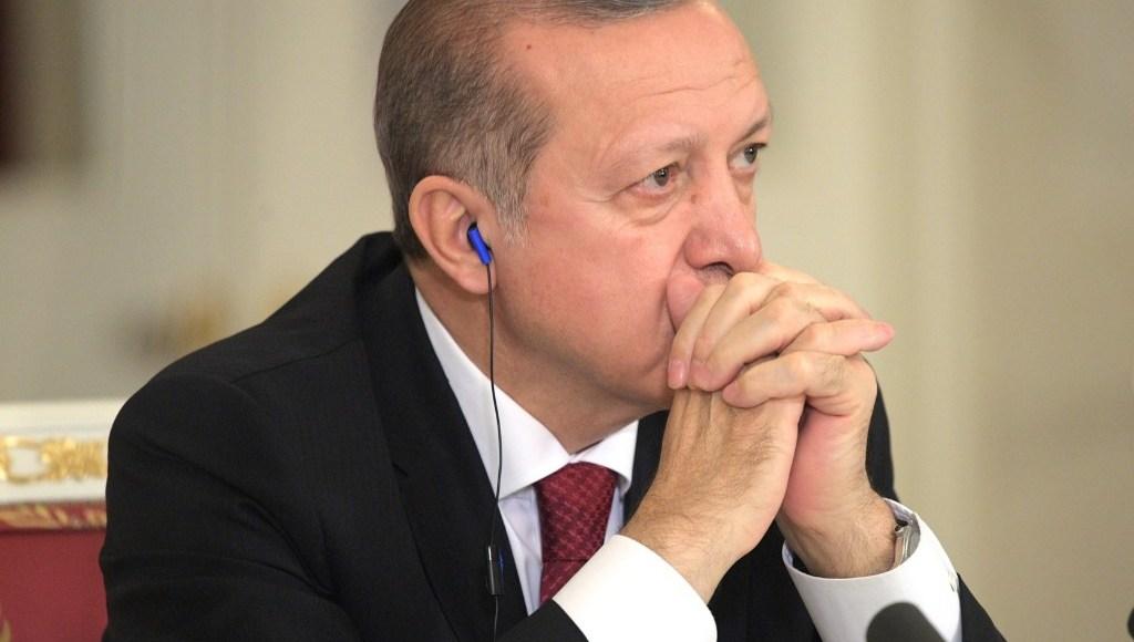 President Recep Tayyip Erdogan listening to a speech with earphones.
