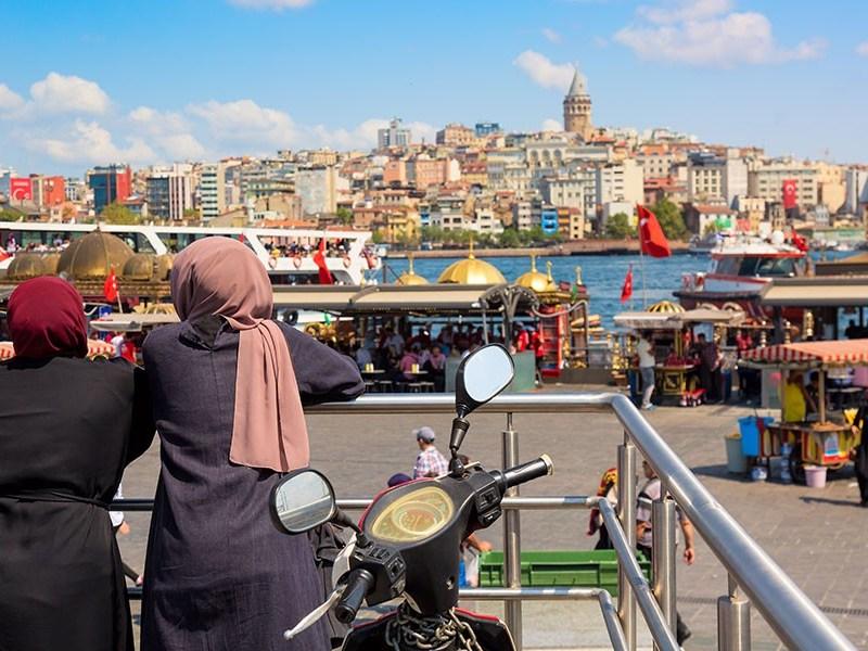 Muslim women looking Istanbul panorama with Galata tower . Istanbul, Turkey.