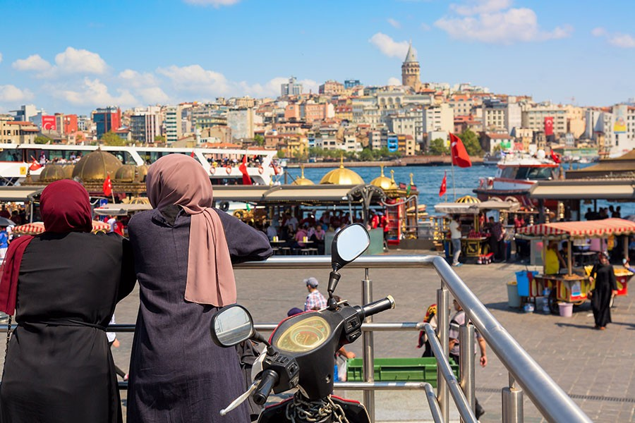 Muslim women looking Istanbul panorama with Galata tower . Istanbul, Turkey.