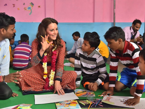 Princess Kate wore a simple red frock, as well as a red tika spot and flower garland, at a boys' charity in Delhi on Tuesday DOMINIC LIPINSKI - POOL/GETTY IMAGES