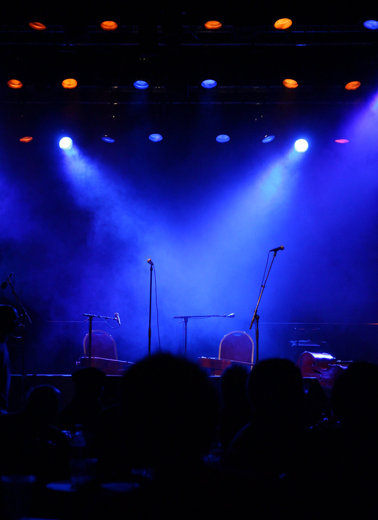 Microphones on unoccupied blue lit stage