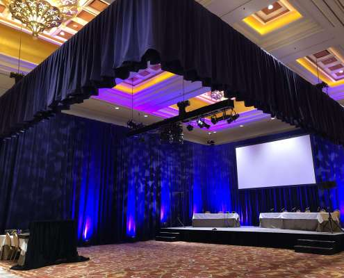Purple Velour / Purple Velvet Rental Drapery Installed By Turn of Events Productions Hung on a Truss. Also Purple Velour / Velvet Drapery from Floor to Ceiling From Turn of Events Las Vegas Rental Drapery