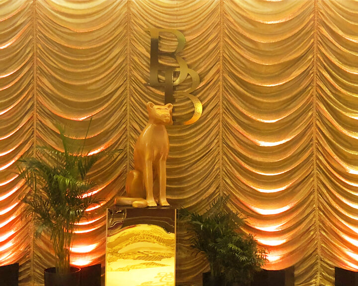 Custom Gold Austrian Drapery Entrance with plants and cat statue from Turn of Events Las Vegas