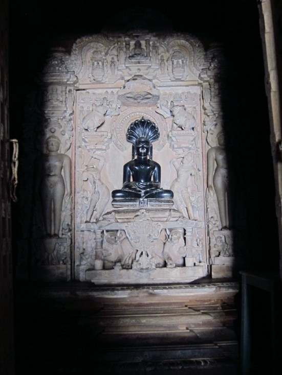 Temple statue in Khajuraho illuminated by a single square of reflected sunlight.