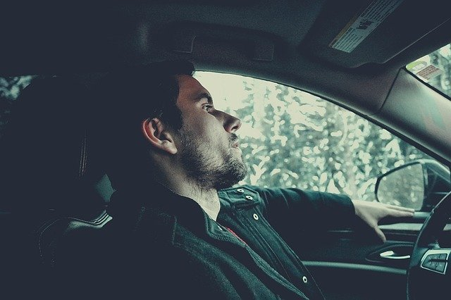Photo of a young white bearded man sat behind the steering wheel of a car