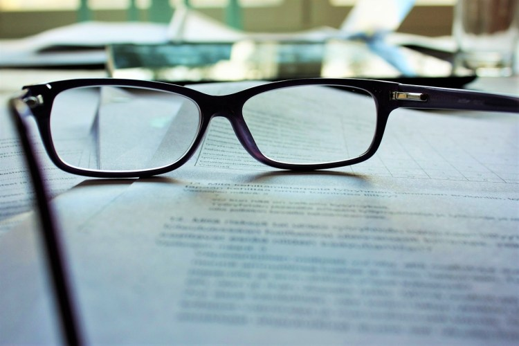 A pair of black rimmed spectacles resting atop some paperwork