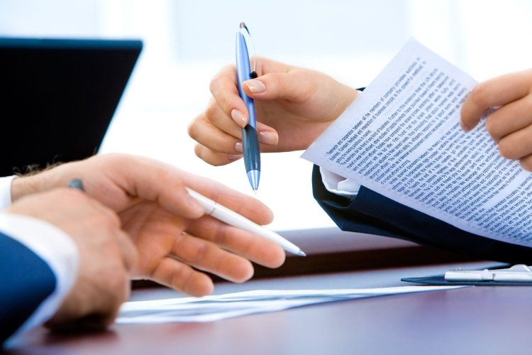 Photo of woman's hand passing a pen to a man, holding a document in her other hand.