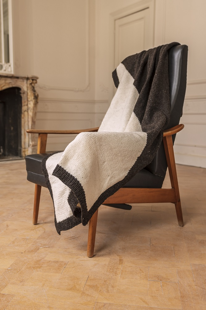 Handmade black & white blanket draped over a black leather chair