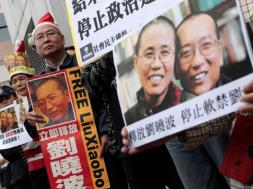 Pro-democracy demonstrators hold up photo of jailed Chinese Nobel Peace Prize laureate Liu Xiaobo during a protest to urge for the release of Liu, outside the Chinese liaison office in Hong Kong