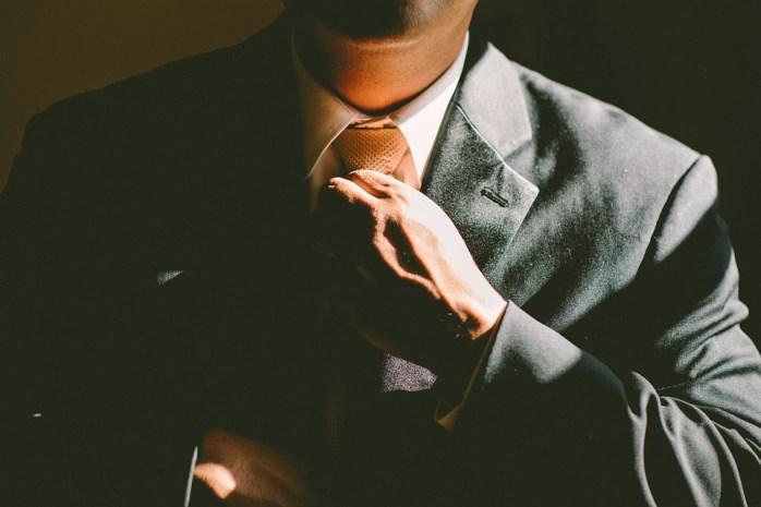 Privlačan muškarac u odijelu steže kravatu oko svojeg vrata
