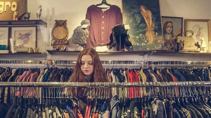 Prvi spoj u shopping centru. Žena riđe duge kose zamišljeno gleda u odjeću na vješalicama.