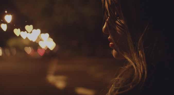 Profil žene tužne zbog prekida na mračnoj ulici po noći.