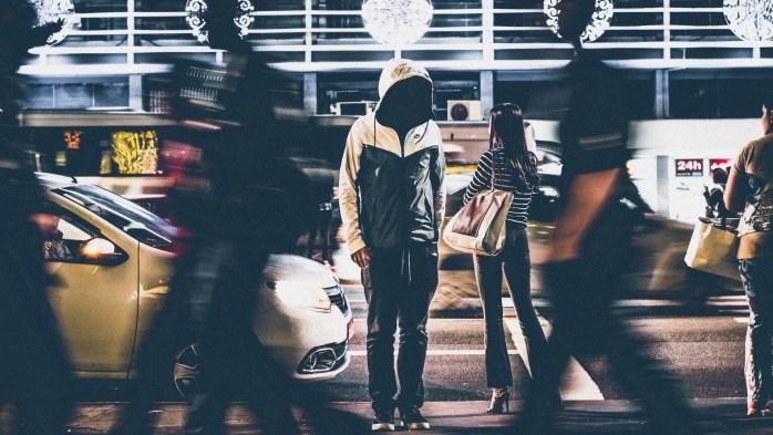 Povučena i sramežljiva osoba kojoj se ne vidi lice prelazi užurbanu gradsku cestu.