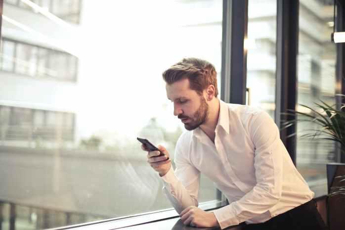 Muškarac u košulji preko mobitela pregledava svoj profil na dating stranici
